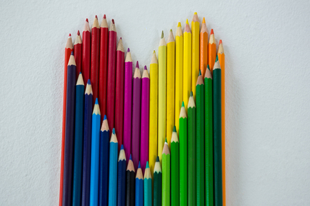 Close-up of colored pencils arranged in heart shape on white background Stock Photo