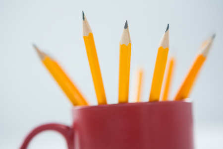 Close-up of yellow color pencils kept in mug on white background Stock Photo