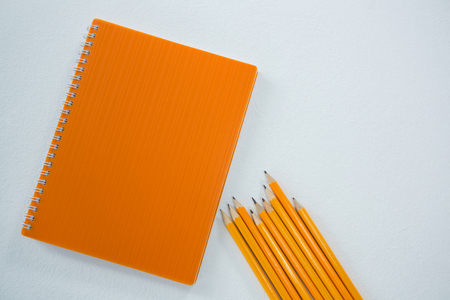 Close-up of yellow color pencils with book on white background Stock Photo