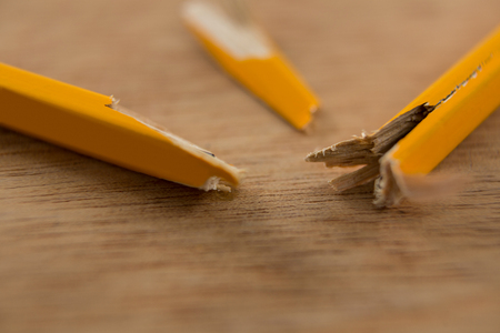Close-up of broken yellow pencil on wooden background