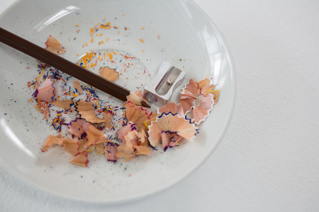 Colored shavings with brown color pencil and sharpener in saucer on white background
