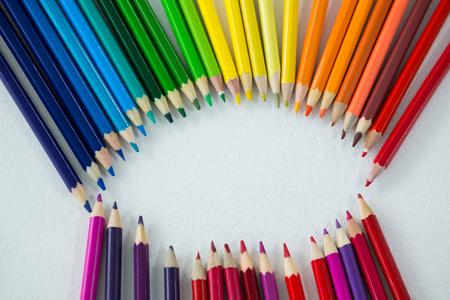 Close-up of colored pencils arranged in circle on white background