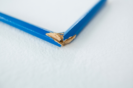 Close-up of broken blue pencil on white background