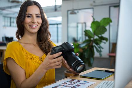 Portrait of smiling female graphic designer holding digital camera in creative office Stock Photo