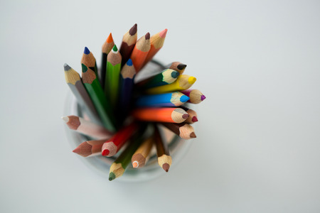 Colored pencils kept in jar on white background
