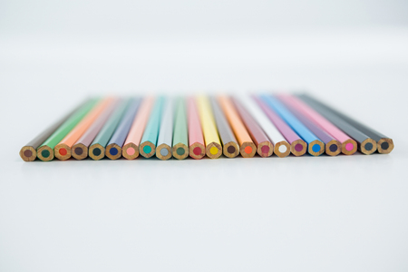 Colored pencils arranged in a row on white background Stock Photo