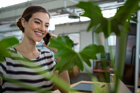 Smiling female graphic designer talking on mobile phone in creative office Stock Photo