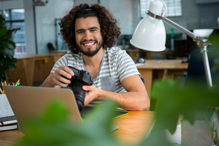 Portrait of smiling graphic designer looking at pictures in digital camera at office