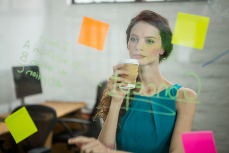 Thoughtful female executive looking at sticky notes in creative office
