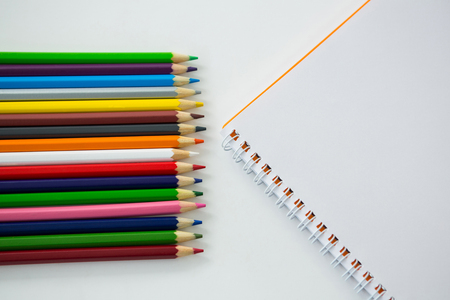 Colored pencils with spiral book on white background