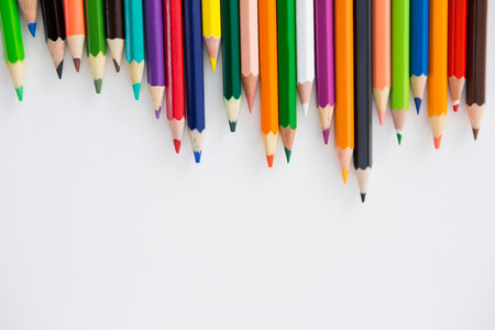 Colored pencils arranged in a wavy pattern on white background