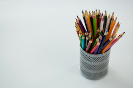Colored pencils kept in pencil holder on white background Stock Photo