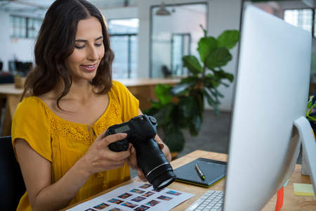 Female graphic designer looking at pictures in digital camera at creative office Stock Photo