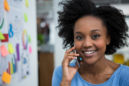 Smiling graphic designer talking on mobile phone in creative office