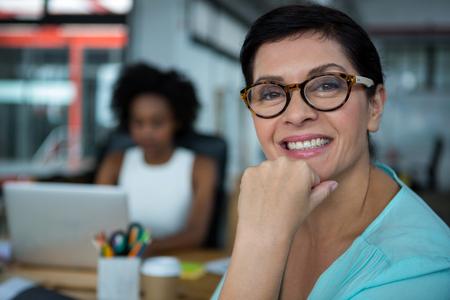 Portrait of female graphic designer in glasses smiling