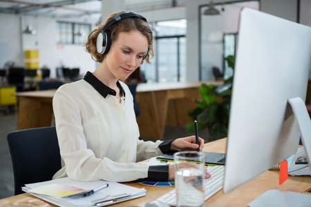 Female graphic designer working at desk in creative office Stock Photo