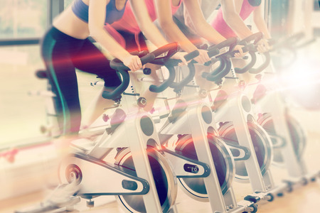 Abstract background against low section of people working out at spinning class Stok Fotoğraf