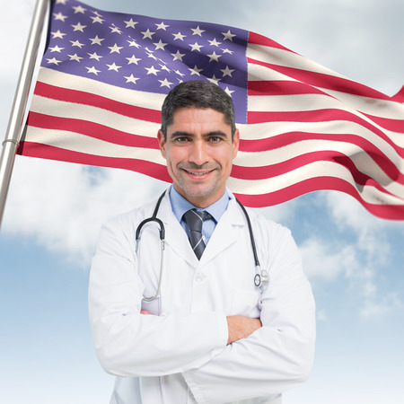 Smiling male doctor with arms crossed in hospital against composite image of low angle view of american flag Stock Photo