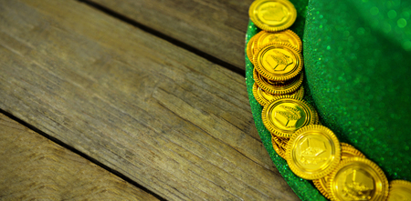 lucky charm: St Patricks Day leprechaun hat with gold chocolate gold coins on wooden wood