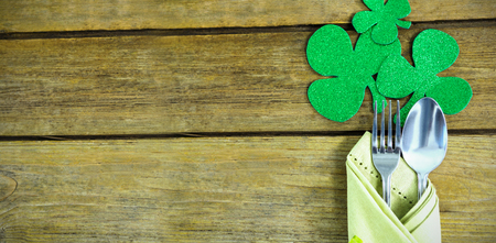 St Patricks Day fork and spoon wrapped in napkin with shamrocks on wooden table Stok Fotoğraf