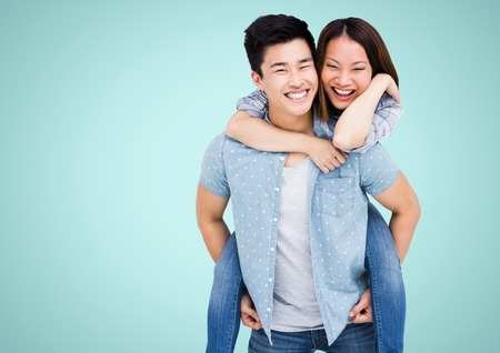 piggyback: Digital composite of happy Asian couple against blue background