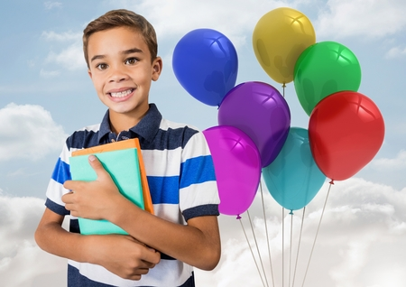 Digital composite of Kid Boy holding books against colored balloons in sky