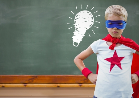 Digital composite of superhero kid against blackboard with lightbulb
