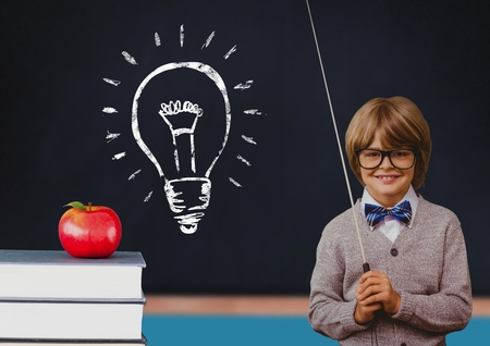 Digital composite of kid at school against a blackboard with lightbulb Stock Photo