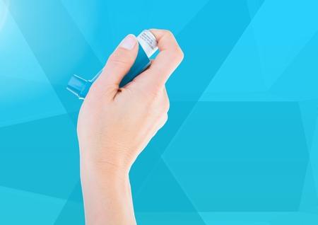 Digital composite of Hand holding Ashtma Inhaler against blue background Stock Photo