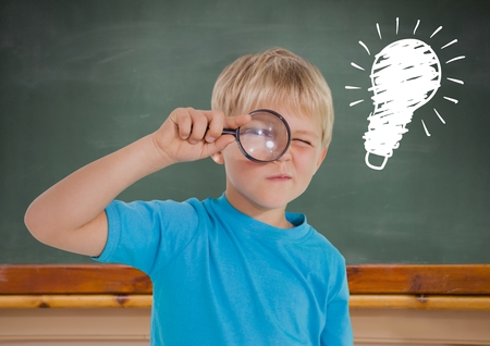 Digital composite of kid looking through magnifiying glass against blackboard with lightbulb Stock Photo
