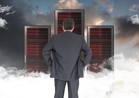 Digital composite of Businessman Standing looking at folders against dark sky Stock Photo