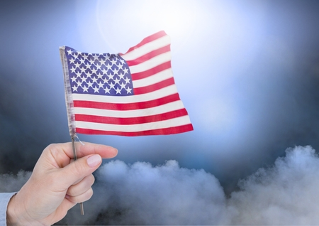 Digital composite of hand holding little American flag against clouds