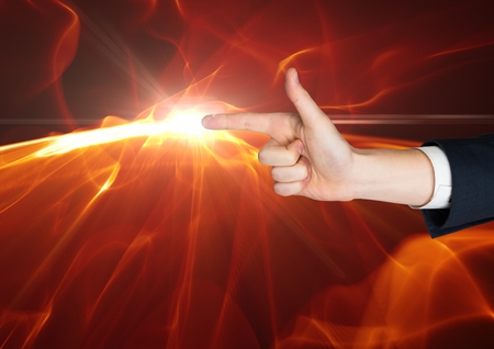 cropped out: Digital composite of Hand as a gun with a flame at the top of the finger against black background