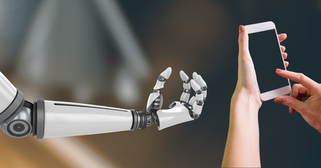 Digital Composite Image of Robotic and Human Hand with phone Interact against dark background Stock Photo