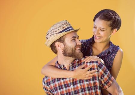 piggyback: Digital composite of Happy Couple Hugging against a orange Background