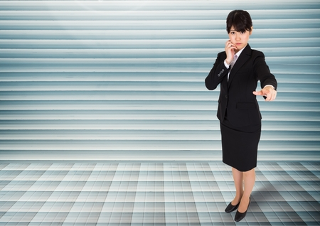 Digital composite of Businesswoman looking and pointing at camera against grey background Stock Photo
