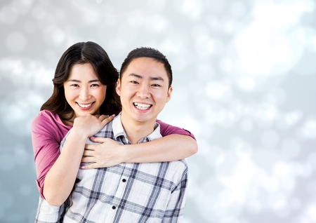 Digital composite of Happy Couple Hug and smilling at camera against a grey Background Stock Photo