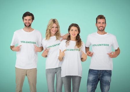 Digital composite of Happy Volunteers Teams pointing at tee shirt against green background