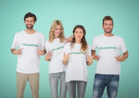 selfless: Digital composite of Happy Volunteers Teams pointing at tee shirt against green background