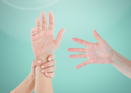 Digital composite of Three Hands holding one against light green background Stock Photo