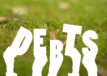 personal perspective: Digital composite of Debt letters against Grass background Stock Photo