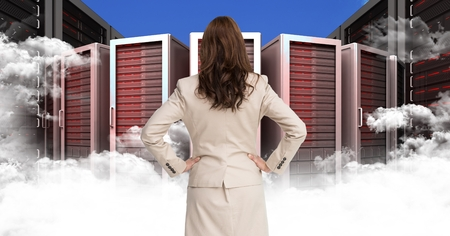 scrolling: Digital composite of Businesswoman Standing looking at Graphic with clouds against a blue background