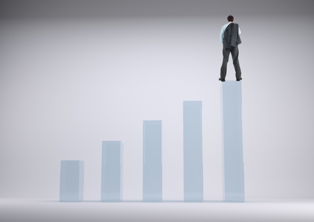 Digital composite of Businessman standing on a graph against a grey background