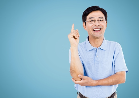 Digital composite of Happy Man raising arm and smiling against a light blue background Stock Photo