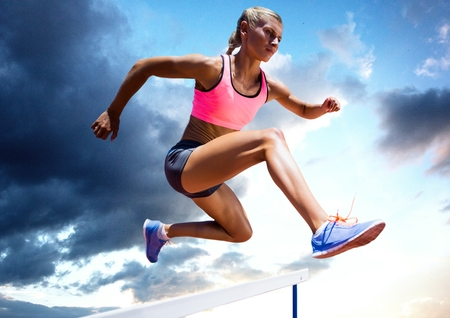 Composite image of athlete jumping over a hurdle against sky in background Stock Photo
