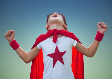 Boy shouting and pretending to be a superhero against blue background Stock Photo