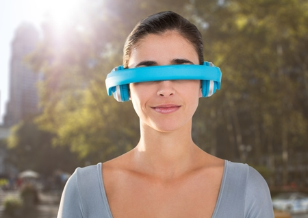 Woman using virtual reality glasses against city street in background Stock Photo