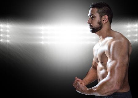 Smart muscular man posing against black illuminated background