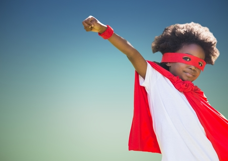 Portrait of boy pretending to be a superhero against blue background Stock Photo