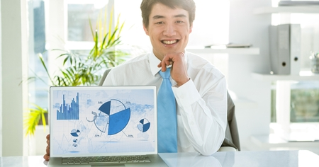 Businessman with laptop displaying graph charts on screen at office Stock Photo